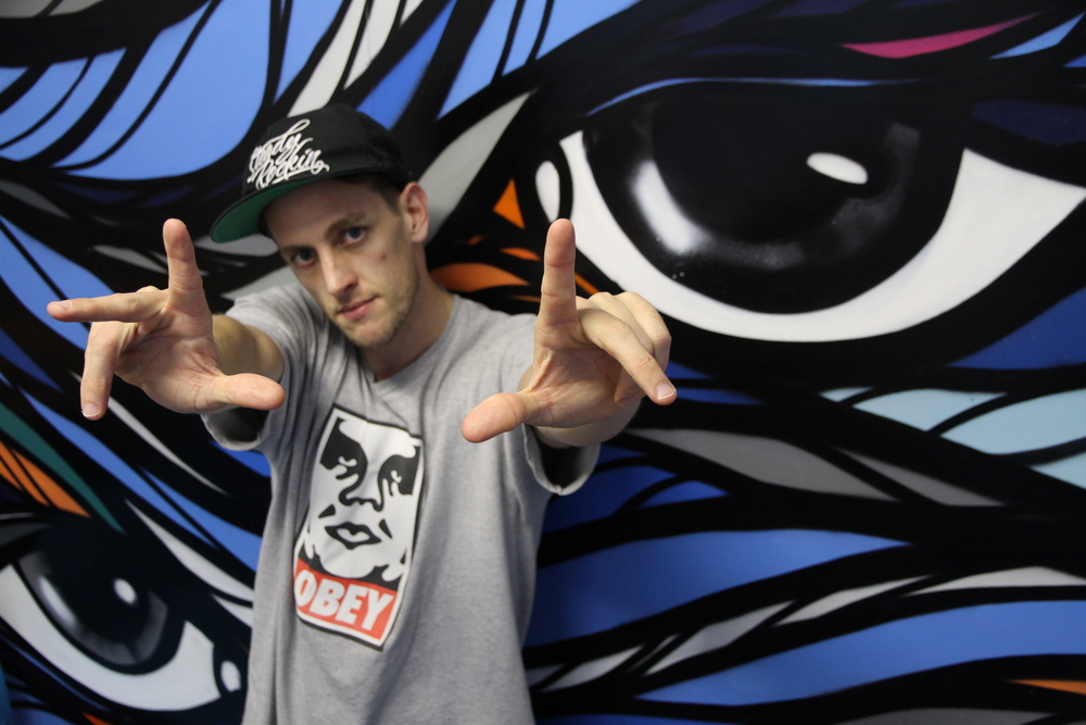 Photo caption: Elementz break dance workshop facilitator Brendan Burns aka B- Boy Beast in front of urban artwork by artist Craig Bond.