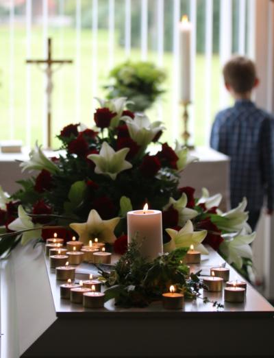 Gæsterne tændte et lys hver og på kisten ligger en lille buket friske krydderurter fra haven, som afdøde elskede så højt.