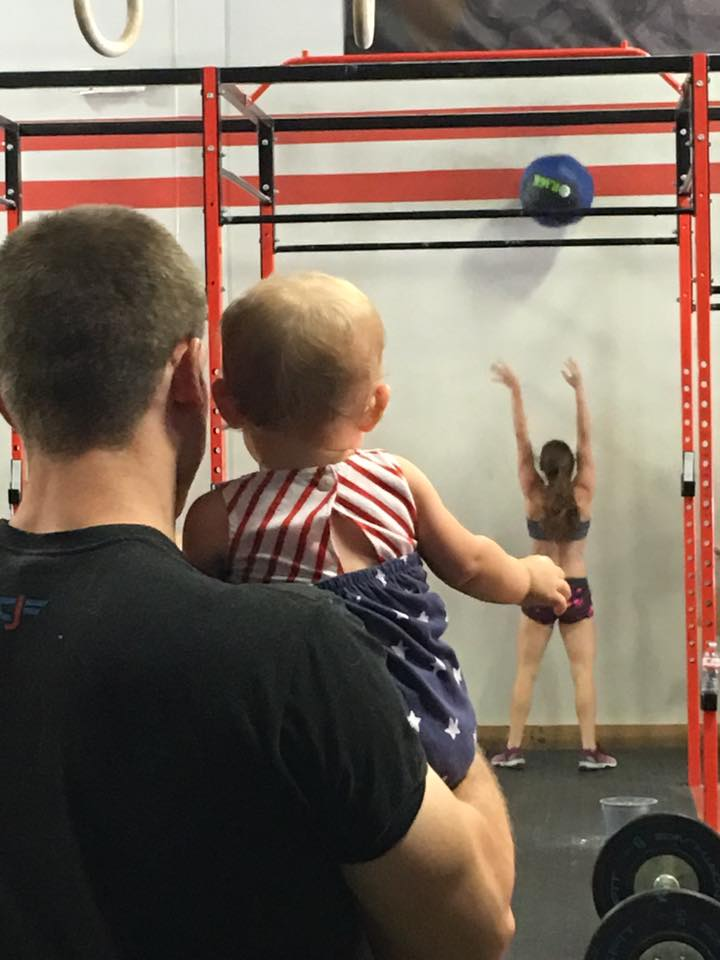 Baby Girl watching her mom power through a WOD at the Goddess Games. Beautiful wall balls, Mo!
