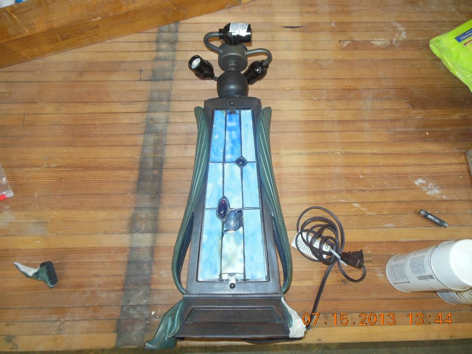 took in a Tiffany reproduction table lamp for replacement of art glass panes in the front panel and repairs to broken leg. Not rare or expensive but still in need or repair..jpg