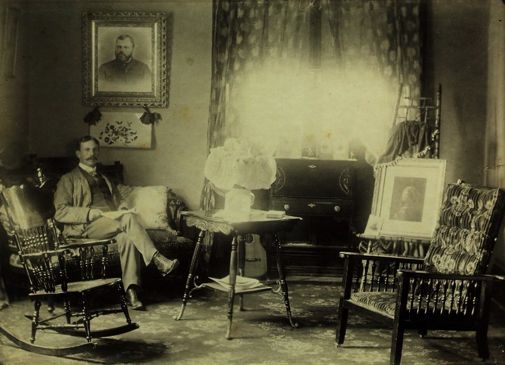 Frank S. Pearce sitting in the northwest corner of the stone house,  in Mrs. Campion's apartment.  On the wall is a portrait of Thomas Pearce.