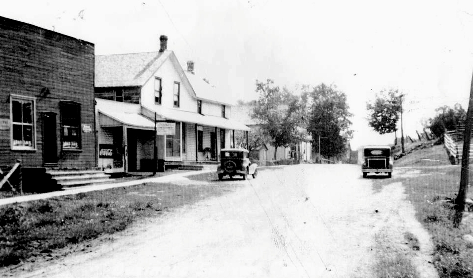 lOOKING WEST C. 1930       Jim Chard adds:   Pool hall in the immediate left of the picture and   ice cream stand, seen between that building and the store, where the laneway is today.       The name was changed from Wariston  because of the discovery of gold, and the ensuing mining operations.
