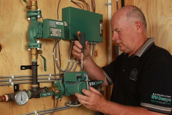 Paul McRoberts finishes a final wire check on the Taco variable speed Delta T 00 circulators at the Brennan residence.