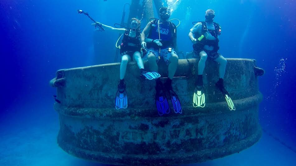 Brooke Linn : Some of my favorite ocean experiences have happened under the surface during my dives in Grand Cayman. Shown here, I am on the stern of the Ex-USS Kittiwake, a former US Navy submarine rescue vessel. On this wreck, I was able to sign one of the very few geocaches underwater! I've also taken lots of Sea Turtle selfies, have been under grottos, gone on night dives and have found octopus that come out to feed, and so much more. I can't wait to finish my Divemaster.