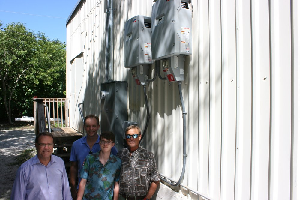 L to R: Dell Jones and Rudy Wodrich of Solar Utility Partners of Estero, Conrad Wodrich, a long-time Sanibel Sea School student, and Dr. Bruce Neill, Sanibel Sea School's Executive Director, pose for a photo with the solar array control panels on activation day.