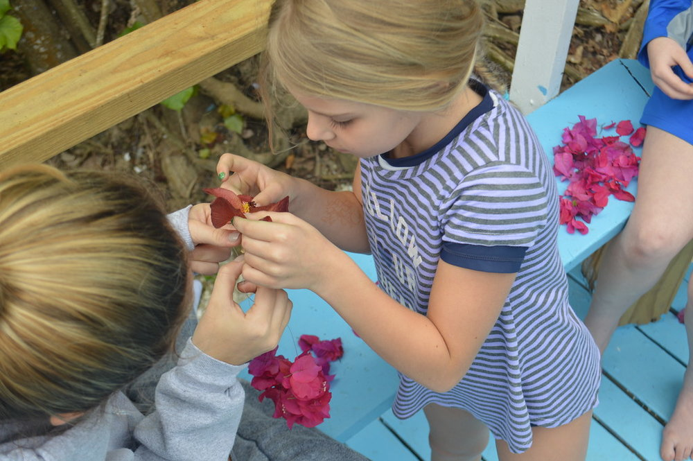A Counselor-In-Training helps a camper create a handmade flower necklace, called a lei, to wear during her hula performance.