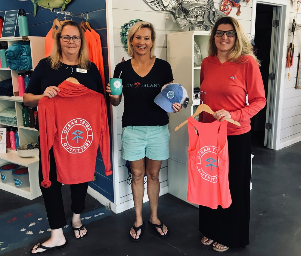 Chrissy Basturk, Kate Sergeant, and Christina Gould display some of the new items available at Sanibel Sea School's Ocean Tribe Outfitters.