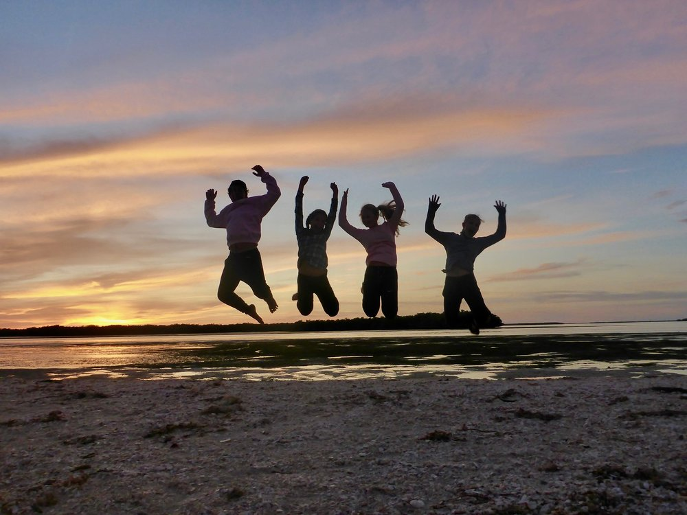 Paddlers jump for joy during a camping expedition to Picnic Island.