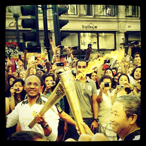 What are the odds that I would be leaving #carnabystreet to stop at a crowd gathering on #regents street realizing that surely the #olympic #torch won't be passing by only to have the passing over of the #flame happen right in front of us!! #fate  (Taken with  Instagram )