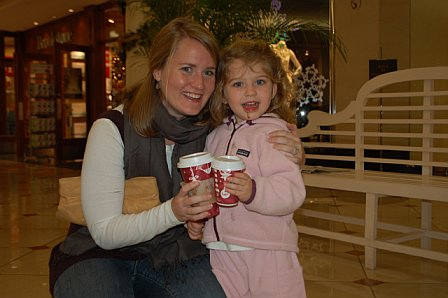 "Sarah Campbell enjoyed her first-ever Starbucks (hot chocolate).  She wanted to ""cheers"" for the picture. Note the chocolate on her chin and all the way down her jacket. I just love being an aunt."