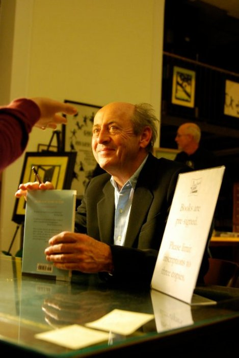 "Here, Billy Collins is asking about where I teach school.  He seems amused…or just tolerant.  Maybe he can sense that we only paid a buck at the Friends of the Library book sale for that first-edition we're having him sign.   I did, however, get to meet him pre-reading when he was trying to find the restroom. That single event sealed our friendship and every other time he saw us that night, he'd say ""you again!""    I particularly liked when he read this poem:    OH, MY GOD   Not only in church and nightly by their bedsides do young girls pray these days  Wherever they go, prayer is woven into their talk like a bright thread of awe  Even at the pedestrian mall outbursts of praise spring unbidden from their glossy lips."