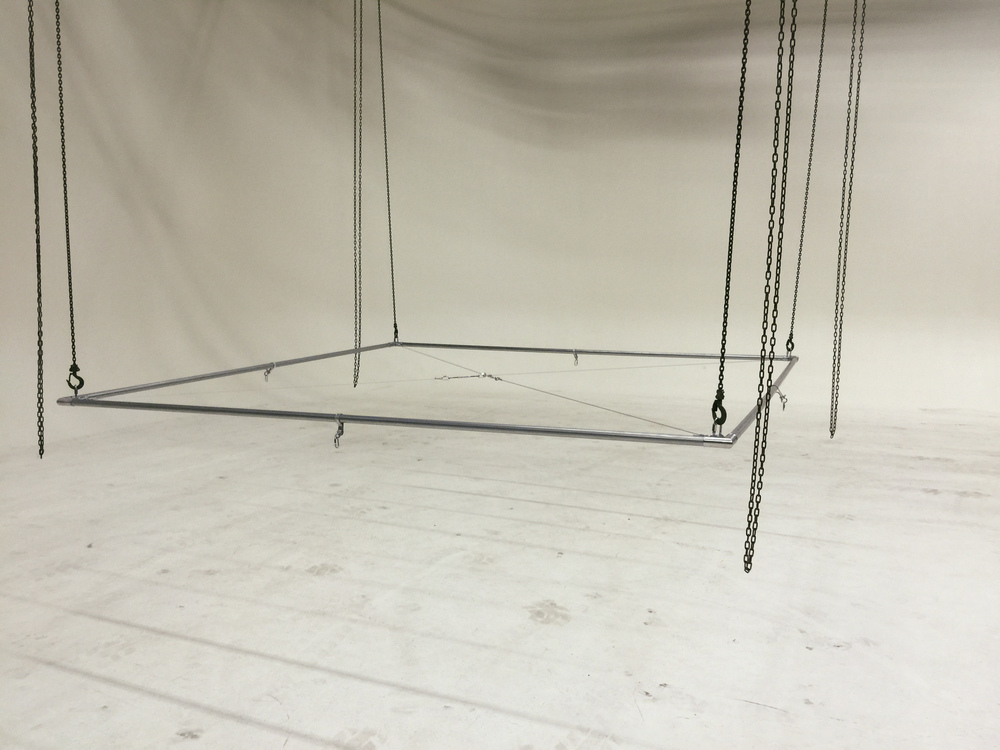 The 10' x 10' lighting rig assembled, cross-braced, and hanging from the chains.