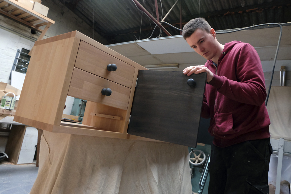 James working on a 'Quatro' with six drawers and two doors finished in a charcoal stain mixed from Farrow and Ball colors.