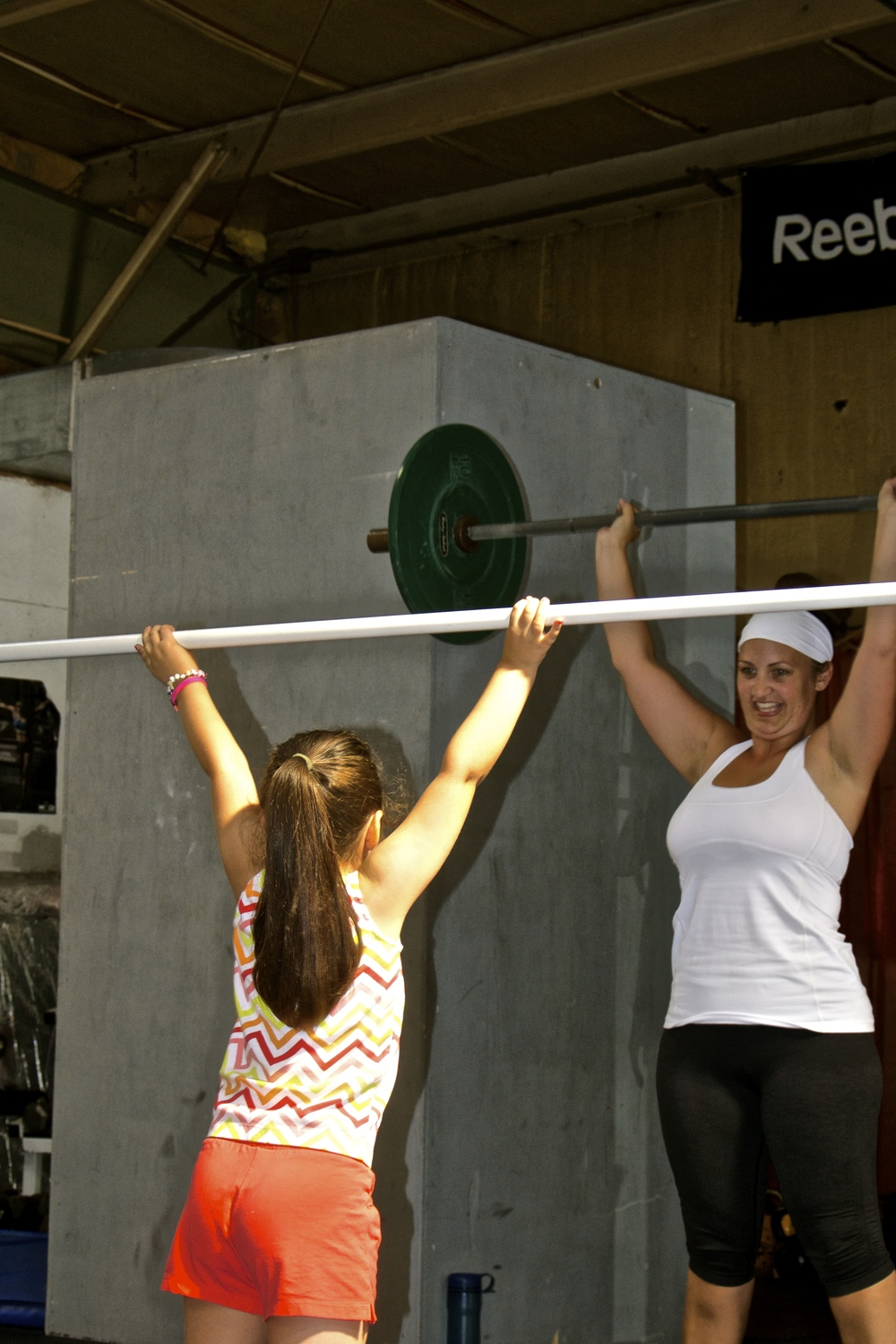 Page and Izzy practice shoulder presses.
