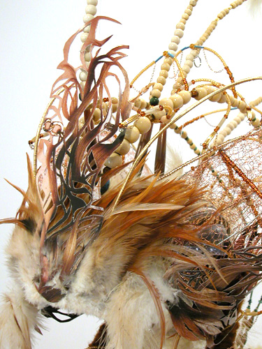 Headdress #1  (detail top), 2006 Metal, foam, jade, turquoise, crystal, glass, bone, wood, clay, metal beads, feathers, gold & copper wire, suede, yarn, copper chain, magazine cutout, and acrylic paint Variable dimensions