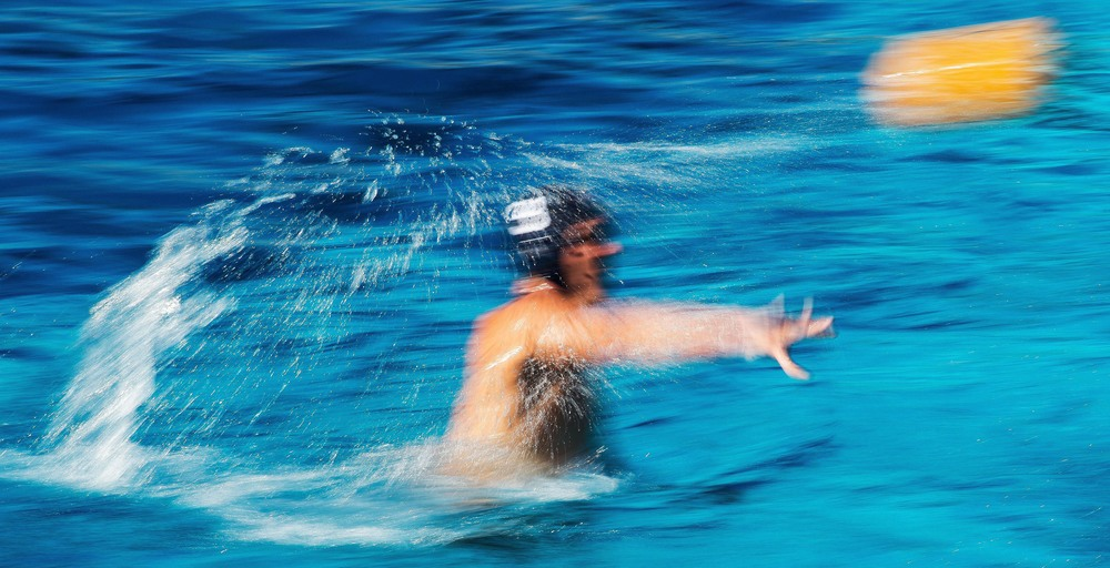 An Orange Coast College men's water polo player passes the ball during a game against Fullerton at Golden West College.