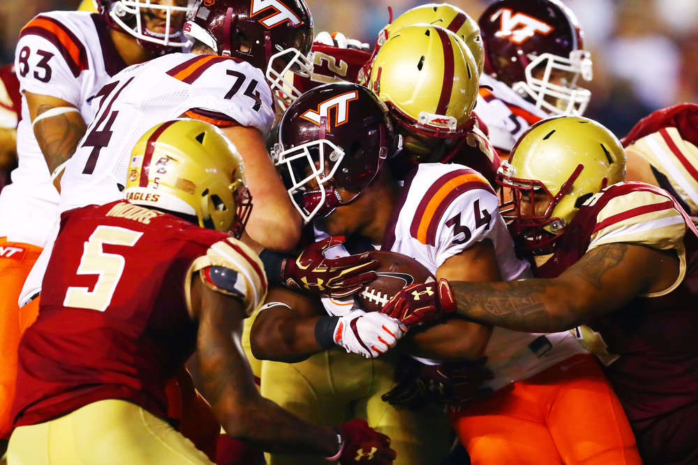 CHESTNUT HILL, MA - OCTOBER 07: Travon McMillian #34 of the Virginia Tech Hokies loses his helmet as he is tackled by the Boston College Eagles defense during the first half at Alumni Stadium on October 7, 2017 in Chestnut Hill, Massachusetts. (Photo by Tim Bradbury/Getty Images)