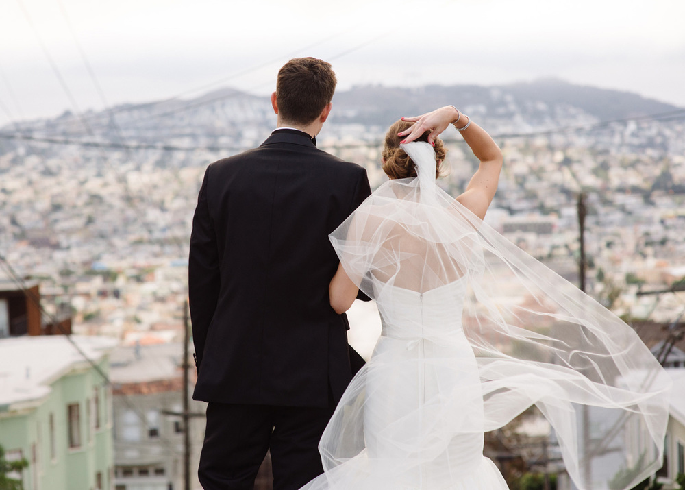Bride and Groom take in the San Francisco urban skyline from Potrero Hill brides veil flows in the wind