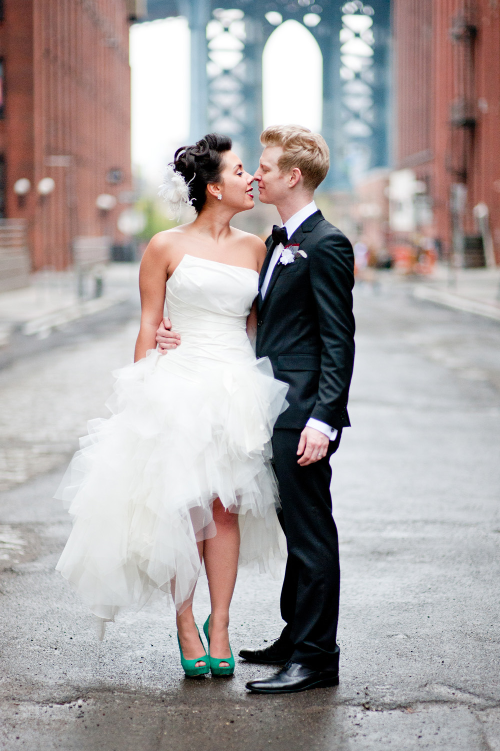 bride and groom embrace on the streets of Dumbo with the Brooklyn bridge behind them