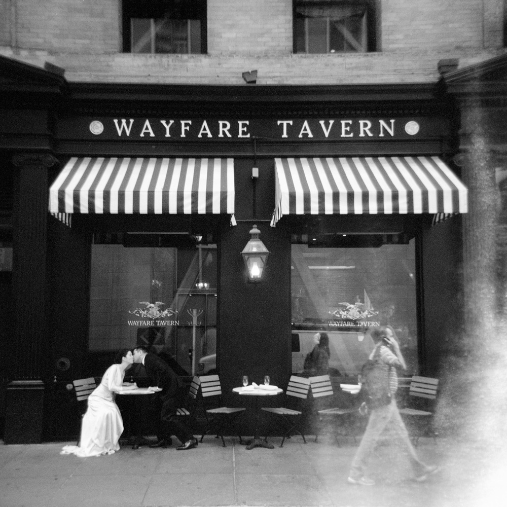 bride and groom share a kiss on a San Francisco sidewalk outside of the Wayfare Tavern. Shot on film with a vintage camera.
