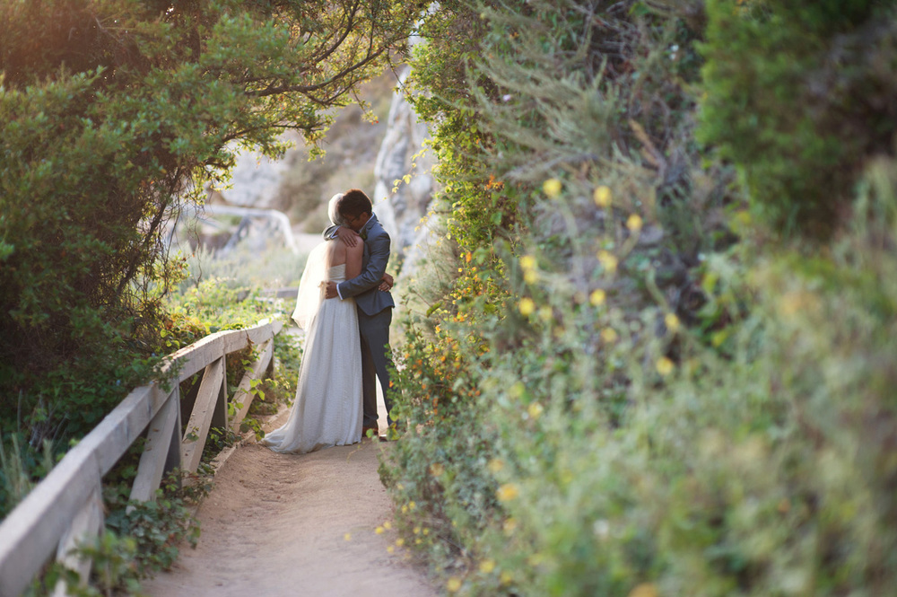 bride and groom embrace on a dirt path on the hillside in Big Sur, California