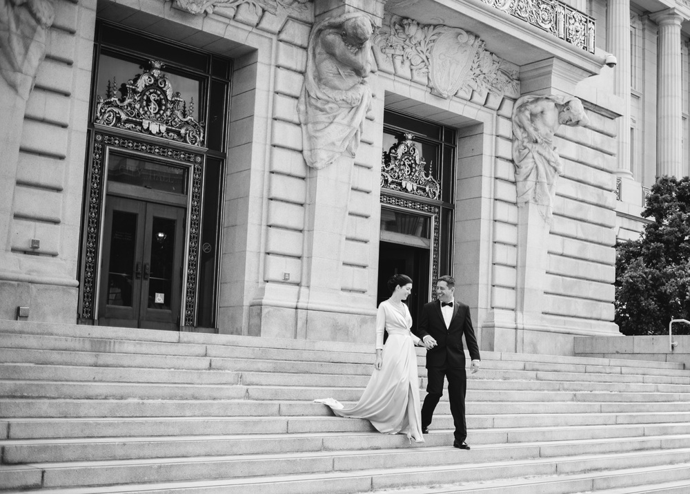 Classic bride and groom descent the outdoor staircase at San Francisco City Hall