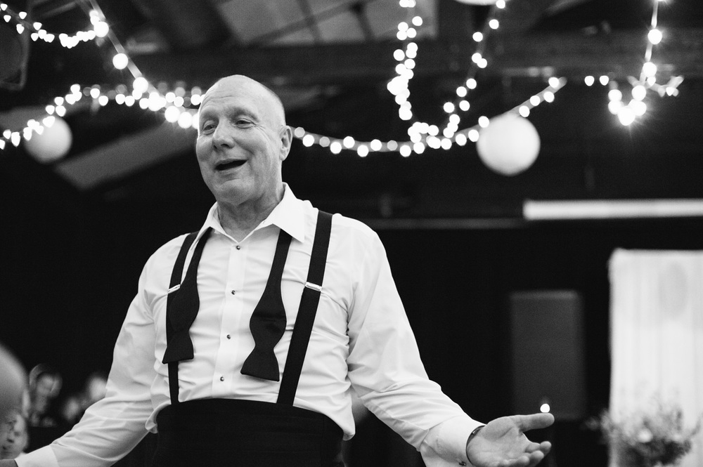 Father of the bride in black tie on the dance floor with twinkle lights behind him