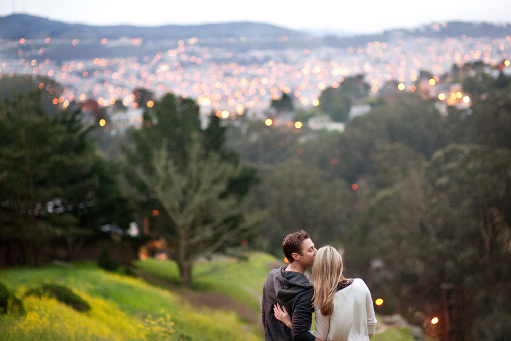 Engagement photo coulple kisses and looks at San Francisco city skyline at dusk
