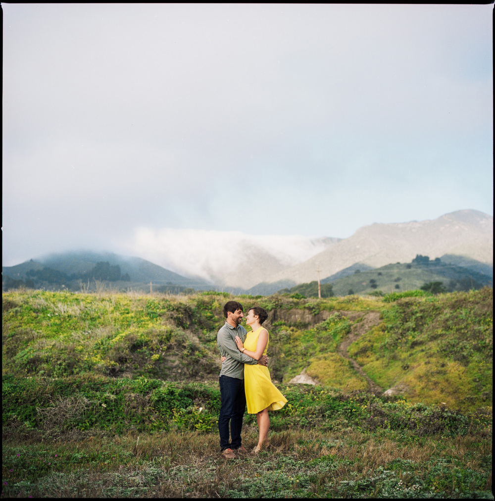 Engagement photo couple embraces each other in the dunes of Montana with fog rolling in over the hills in the distance