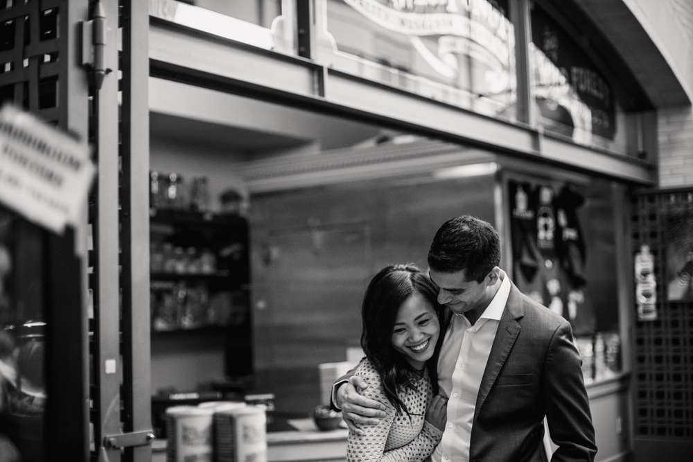 natural engagement photograph couple hugs in the ferry building in San Francisco