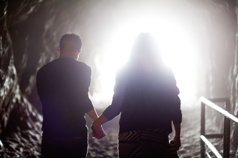 engagement photo couple holds hands and heads into the light at the end of the tunnel