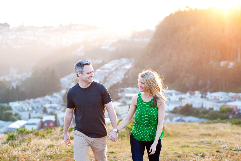 engagement photo couple holds hands and walks in twin peaks in San Francisco at sunset