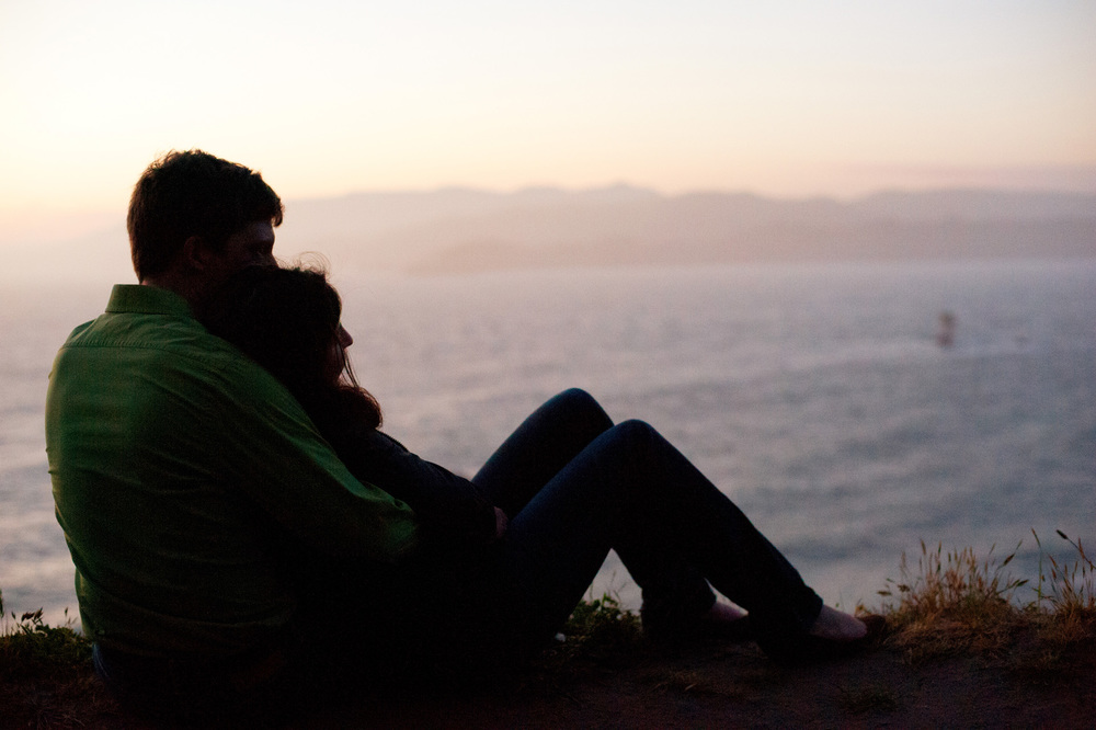 engagement photo couple in silhouette watches the sunset at lands end in San Francisco