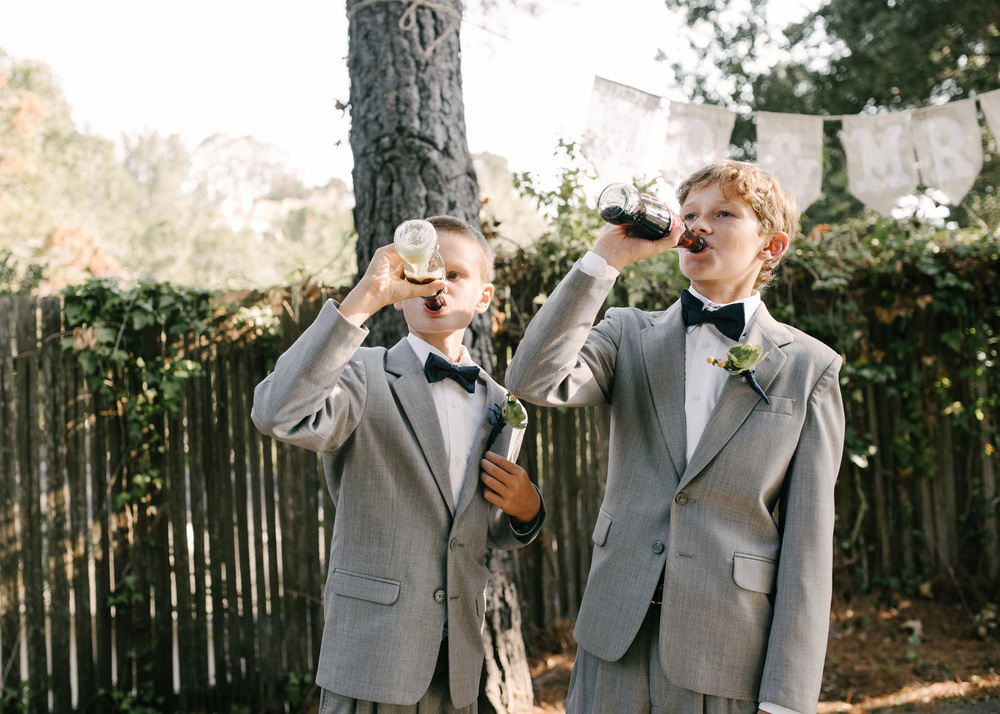 two ring bearer's drinking classic coke during a wedding reception  photography in documentary style