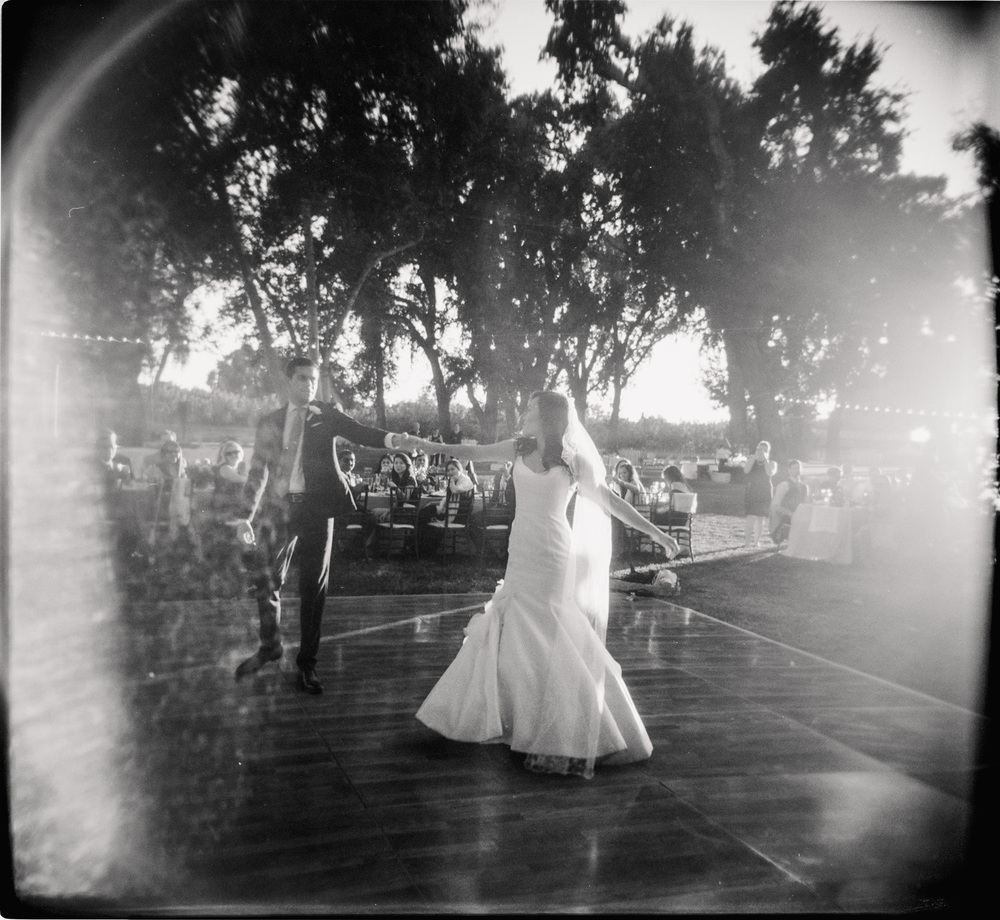 bride and groom outdoor first dance shot on film with vintage camera in black and white in documentary style