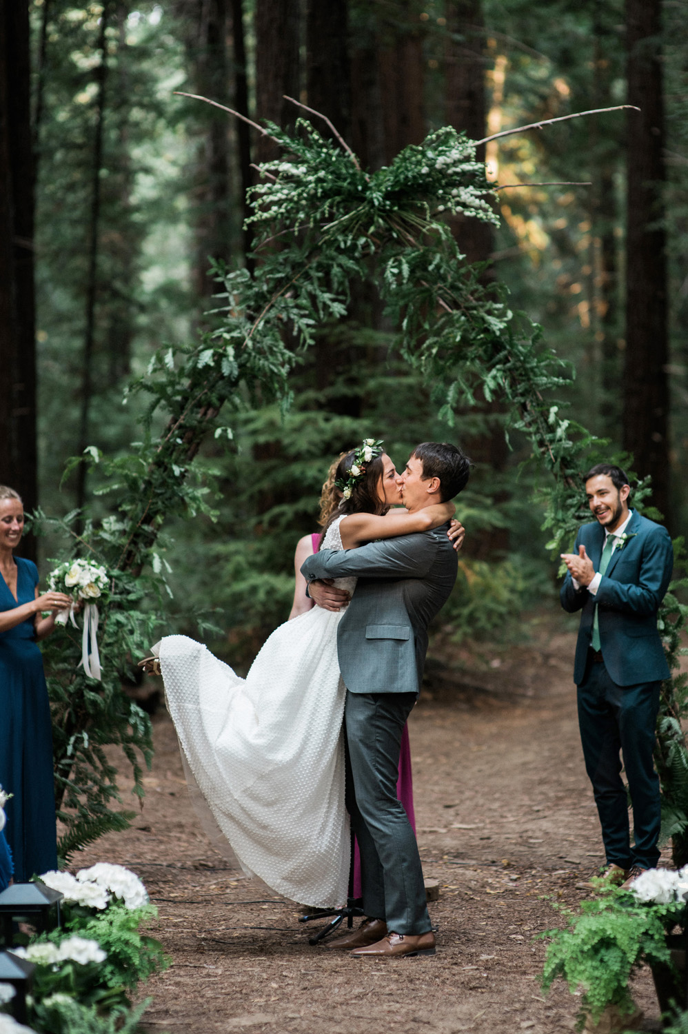 Bride and groom embrace and kiss during their wedding ceremony in the redwood forest in Navarro, CA
