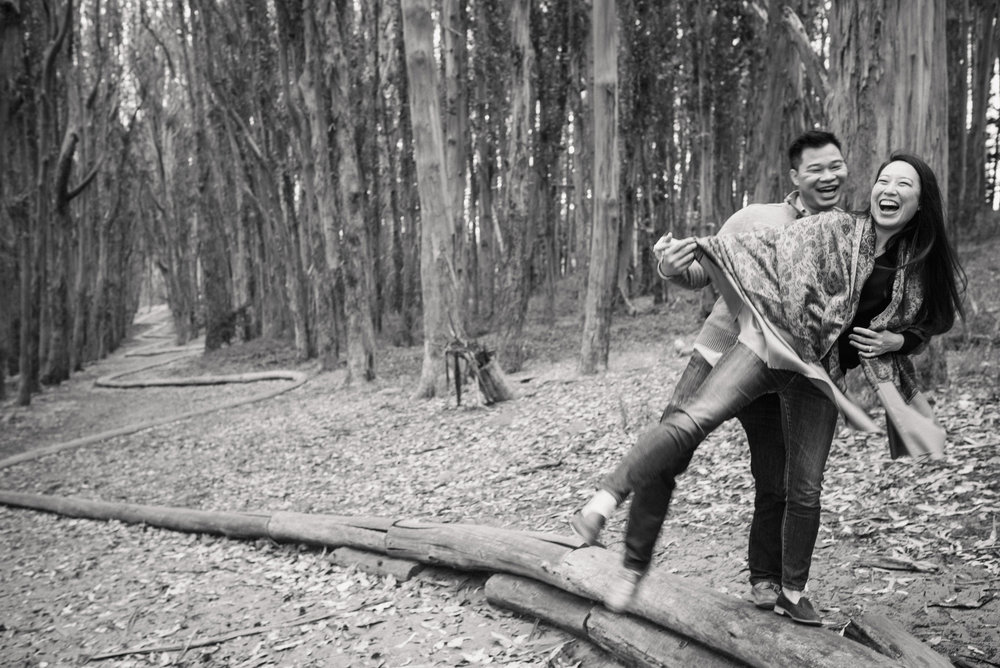 engagement photo couple laughing at the woodline in San Francisco Presidio