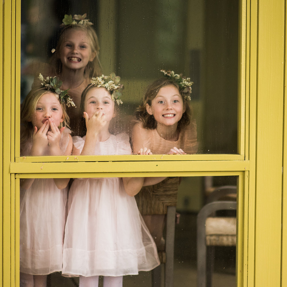 flower girls in window making a kiss gesture Boston documentary wedding photography