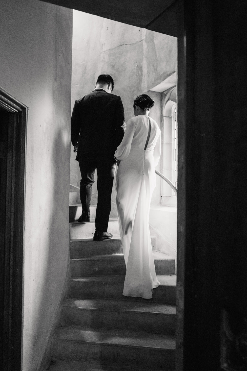bride and groom walk up the stair of a church black and white wedding photography