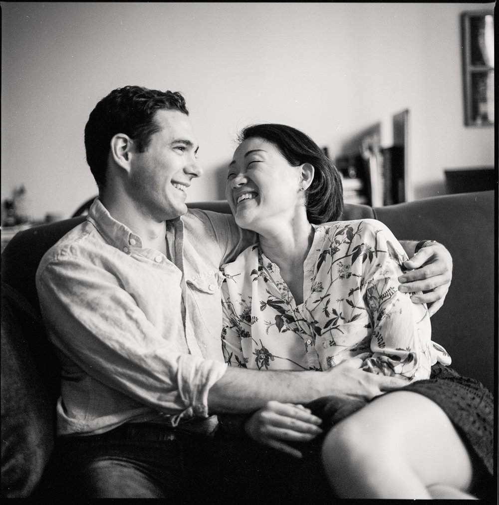 engagement photo couple sits on couch at home black and white film