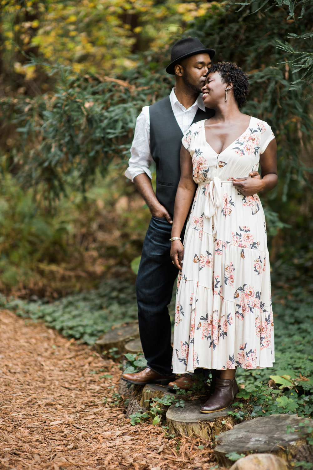 engagement photo couple embraces in garden forest setting