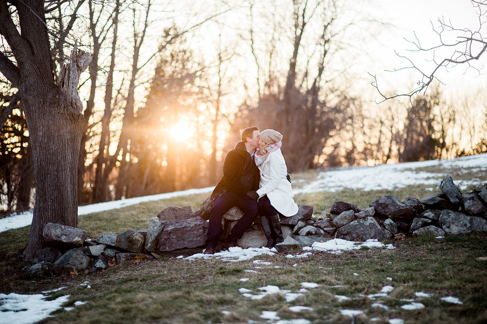winter engagement photo at worlds end in hingham couple sits on stone wall and shares a kiss at sunset