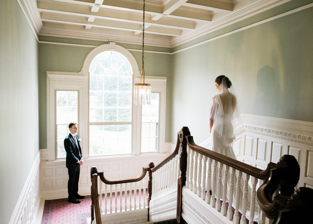 Bride on her wedding day walks down the grand staircase at the historic Lyman Estate in New England