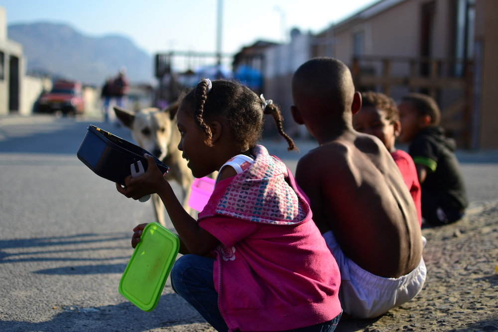 Children enjoying a hot meal on the curb at the Restoring Hands soup kitchen.
