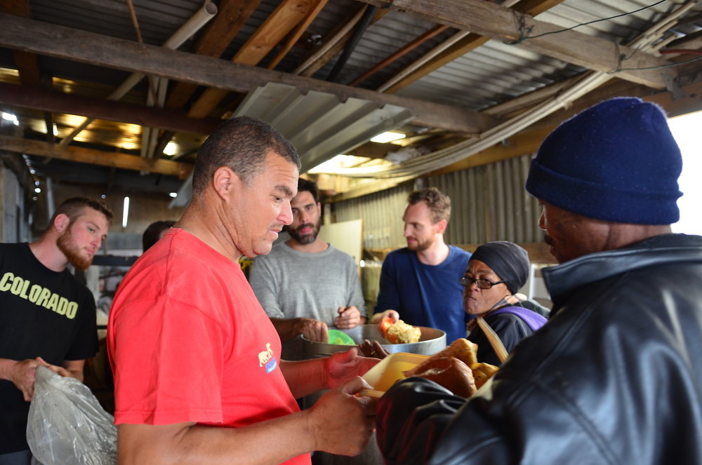 Pastor Edwin giving food to a local Lavender Hill man.