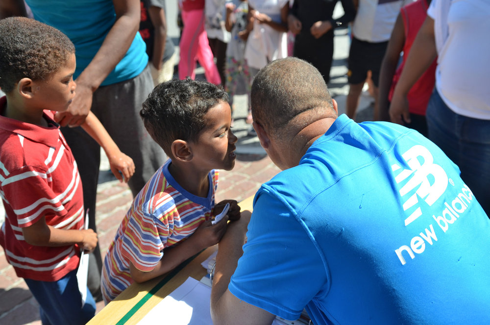 A child whispering to Edwin prior to receiving his school supplies package.
