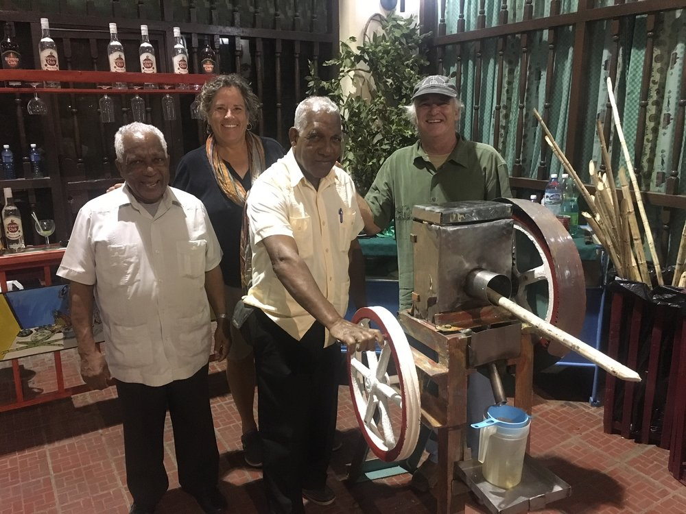 "These gentlemen were anxious to share their sugarcane hand-operated press. They handed us a glass of fresh raw sugar cane juice , which was delicious, smooth and not too sweet. Then they poured a shot of rum in it and said ""try it now!""."