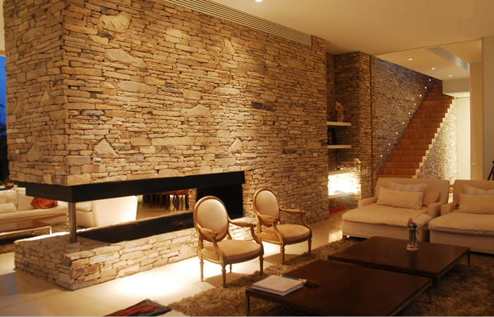 barrionuevo sierchuk agua house stone fireplace wall timber stairs warm contemporary interior design