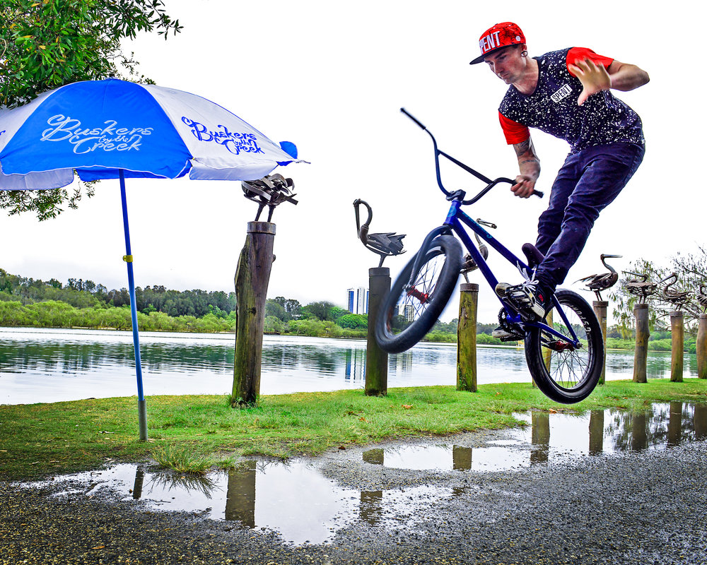 Spent BMXer, Chris James, performs tricks on Australia's FIRST EVER floating half-pipe at Buskers by the Creek in 2016. Photo credit: Andrew Radford Photography.