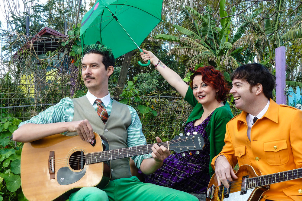 "THE VEGETABLE PLOT (AUS)  The Vegetable Plot is an award-winning live music act that has been spreading its funky roots all over Australia. Serving up a big wriggling heap of catchy tunes, colourful characters, quizzes, dances, jokes and truly rotten puns, these veggie superbeings are on a mission to change the way people think about both vegetables and ""kid's music"". Come and join Aspara Gus, Ru Barb, and Sir Paul McCarrotney for a ride on the soil train!"
